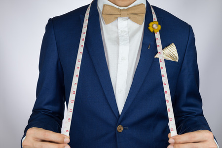 suit: Man in blue suit with coffee cream bowtie color, flower brooch, and dot pattern pocket square carry measurement tape