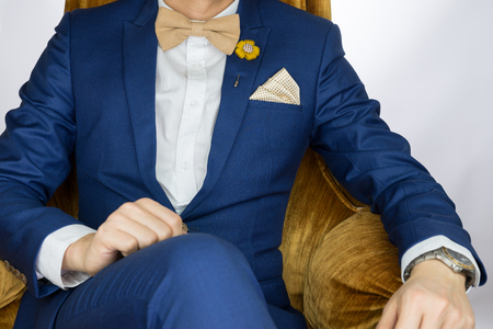 navy blue suit: Man in blue suit with coffee cream bowtie color, flower brooch, and dot pattern pocket square sitting on cozy sofa