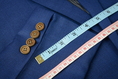tailor suit: white measurement tape on blue jacket, tailoring