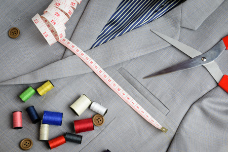tailored: cutting, tailored equipments on double breasted suit, measurement tape, scissors, thread coil Stock Photo