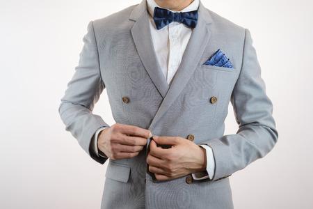 회색 양복, 격자 무늬 질감, 파란색 bowtie 및 포켓 스퀘어 남자, 흰색 배경 위로 닫습니다 스톡 콘텐츠