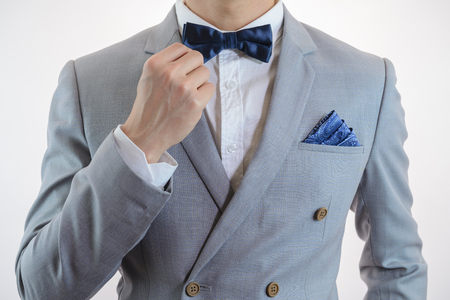 Man in grey suit, plaid texture, blue bowtie and pocket square, close up white background Imagens