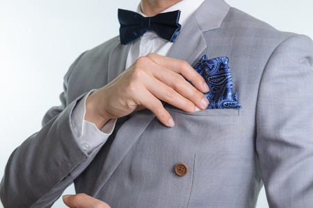 tailored: Man in grey suit, plaid texture, blue bowtie and pocket square, close up white background Stock Photo