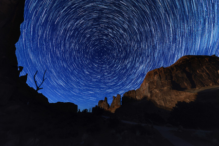 worl: Circle light of star trails at Arches National park, Utah USA, huge rock as a fore ground