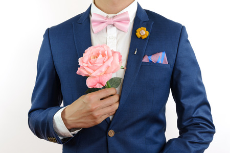 navy blue suit: Man in blue suit with pink bow tie, flower brooch, and pink blue strip pocket square, close up, carry flowers