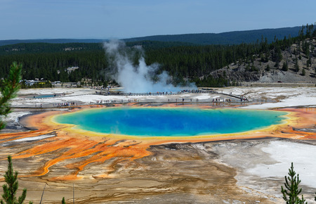Famous trail of Grand Prismatic Springs in Yellowstone National Park from high angle view. Beautiful  hot springs with vivid color blue green orange in Wyoming. A lot of people vitsit the gorgeous Grand Prismatic Springs during summer. Stock Photo - 64577803