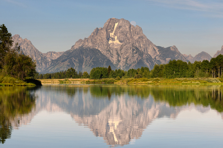 oxbow: Beautiful Grand Teton mountain flecting on a smooth water surface with moonset behind the rock mountain. Oxbow Bend famous scenic point in Grand Teton National Park Wyoming USA.