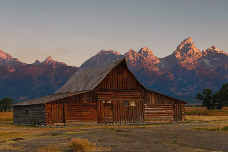 Mormon Row historical site in Jackson, Grand Teton National Park, Wyoming. Moulton Barn at first sunlight touches the Gran Teton peak with a beautiful old barn in summer