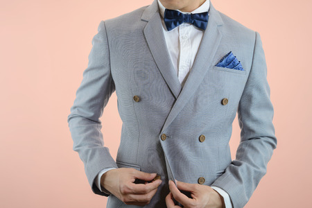 double breasted: Man in grey suit, plaid texture, blue bowtie and pocket square, close up white background Stock Photo