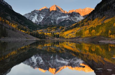 Beautiful sunrise touches Maroon bells peak at Maroon lake, Aspen, Colorado. Fall color of Aspen and reflection of Maroon Bells 免版税图像