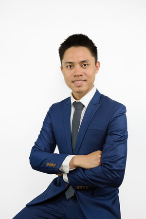 Asian man wearing blue suit and necktie smiling and cross his arms. Short hair cut. Standard-Bild
