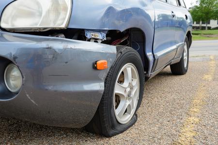 자동차 사고, 펑크 난 타이어, 깨진 범퍼. 오래된 차.