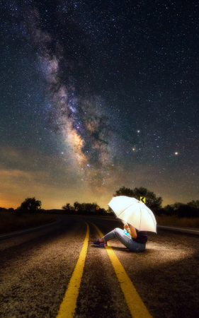 Imagination and connection concept. A woman sitting on a road under the beautiful dark sky and milky way