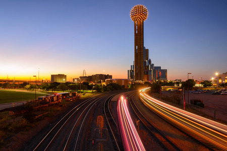 Beautiful sunset and Reunion Tower with light trail of train and railway. Dallas skyline, Texas. Tall building Publikacyjne