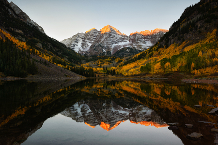 Beautiful sunrise touches Maroon bells peak at Maroon lake, Aspen, Colorado. Fall color of Aspen and reflection of Maroon Bells Stock Photo