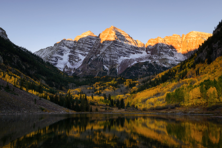 Beautiful sunrise touches Maroon bells peak at Maroon lake, Aspen, Colorado. Fall color of Aspen and reflection of Maroon Bells Imagens