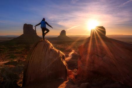 Alba a Monument Valley, Arizona - Utah State Line. Un uomo del viaggiatore esprime emozione di libertà su una grossa roccia antica dei Mittens. Archivio Fotografico - 89137407