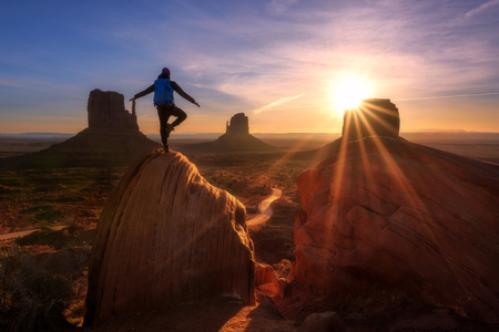Sunrise at Monument Valley, Arizona - Utah state line. A traveller man express freedom emotion on a big rock ant the Mittens. Stock Photo