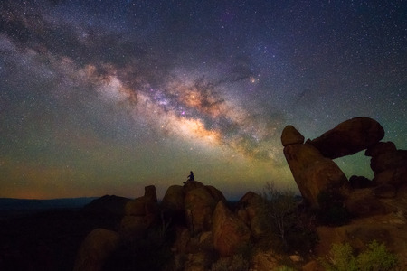 Human observing Milky way at Balanced Rock, Big Bend National park, Texas USA. Constellation and galaxy