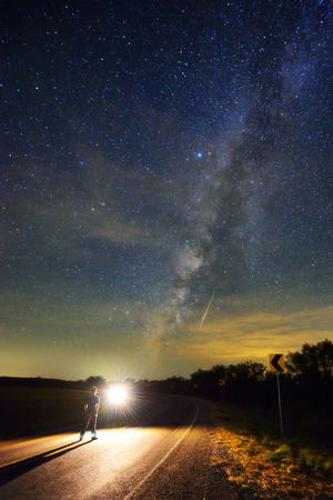 Faint milky way and a man facing spot light.