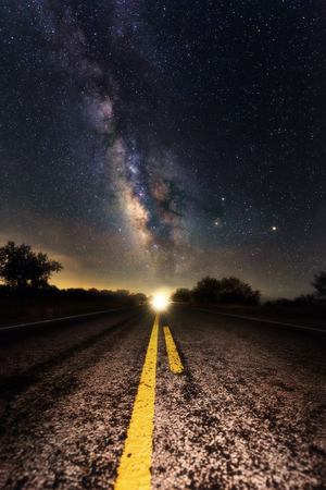 Milky way appear on the middle of the road with double solid yellow line point to the milky way core. Scenic road at night time driving to heaven theme. Outdoor activity at night with bright milky way