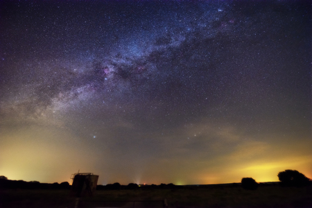 Beautiful night sky with vivid milky way. Yellow light polution at horizon. Astronomy dream dark sky. Stock Photo