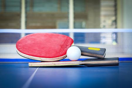 ping pong: Raquetas de ping-pong y la pelota, mesas de ping pong azules. Mesa de tennis. Para hacer ejercicio y mantenerse saludable. Foto de archivo