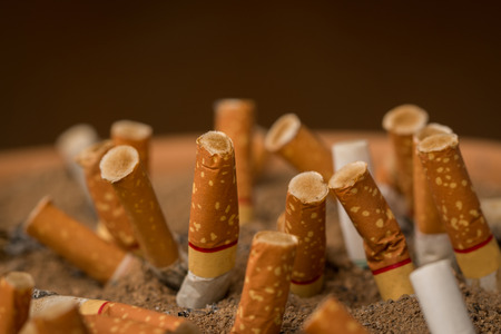 Pollution,Smoking,Danger,Brown ashtray with cigarette stubs in closeup.