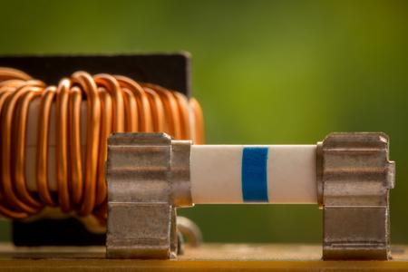 electromagnetism: Electromagnetic coil, inductor. Small winding coils and fuses are mounted on a baseplate. Background.