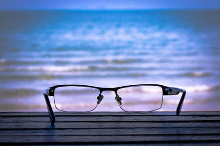 glasses ; spectacles,Van Eyed on a wooden floor. The background is sea blurred. Standard-Bild - 102915492
