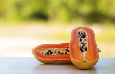 Healthy papaya, food and fruit placed on a wooden table in the warm natural morning.