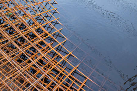 The rusty steel grid in pattern,Rusty construction metal mesh. Rusty Metal armature net for  road infrastructure  metal rebar for construction,Sites Soak in Water and Rust.
