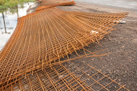 The rusty steel grid in pattern,Rusty construction metal mesh. Rusty Metal armature net for  road infrastructure  metal rebar for construction,Sites Soak and Rust,on Soil road construction. Stock Photo