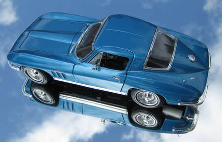 1965 blue Corvette metal toy  car on a mirrored isolated sky background Stock Photo