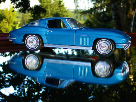A mirrored reflection of the passenger side of a blue 1965 Chevrolet Corvette
