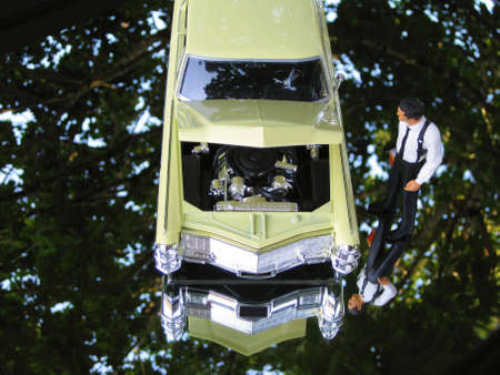 A business man is looking into engine of a car isolated on a mirrored background. Stock Photo