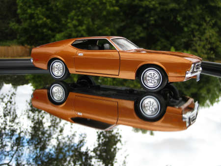 A mirrored reflection of the passenger side of a root-beer colored 1971 classic car . Imagens