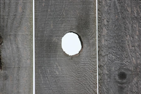 Open Round Knot Hole On Weathered Textured Wood Fence Exposing White Background For Copy Space And Framing