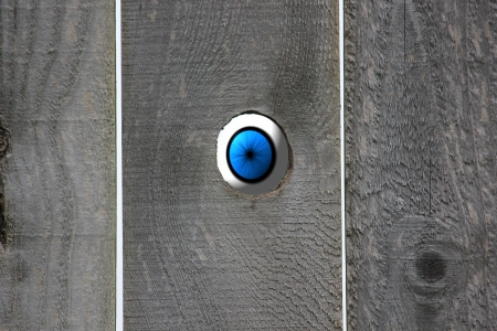 Blue eyeball looking in through an open knot hole in a weathered wooden fence
