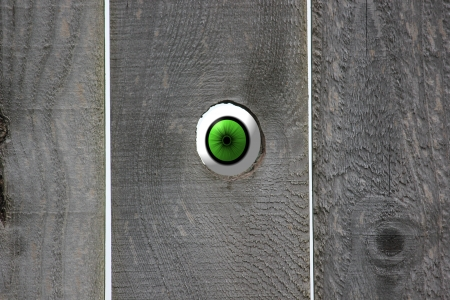 Green eyeball looking in through an open knot hole in a weathered wooden fence leaving room on the fence for your saying