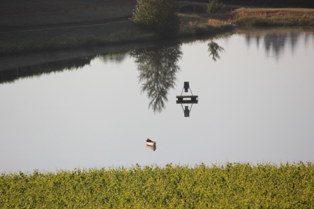 Empty canoe floating aimlessly during early morning sunrise on a still pond showing calm reflections