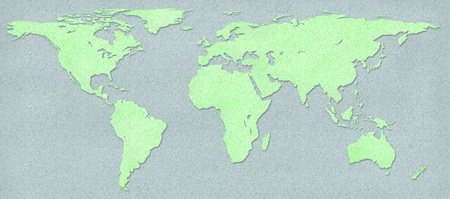 Green world map and earth globes on gray cork board background photo