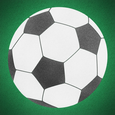 Football soccer ball by cork board on green grass