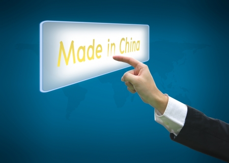 Business hand pointing made in china word on button with world map background photo