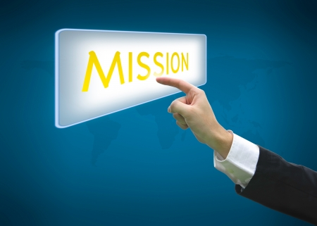 recive: Business hand pointing mission word on button with world map background Stock Photo