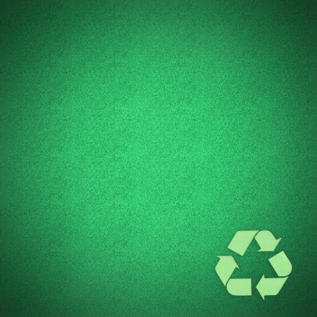 Green recycle logo craft on green grass by cork board photo