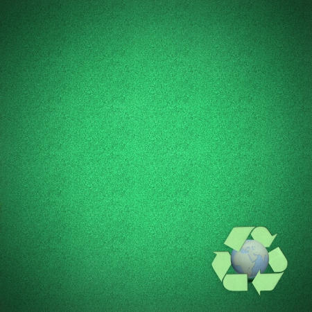 Green recycle logo with globes craft on green grass by cork board photo