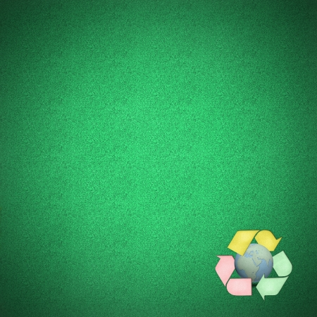 Color recycle logo with globes craft on green grass by cork board photo