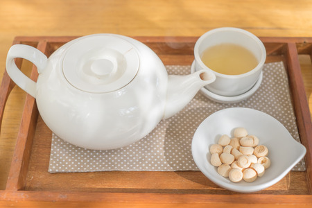 Tea cup pot with sweetmeat on the wooden plate