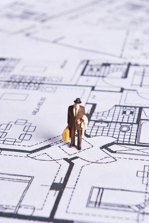 miniature man on plans document photo
